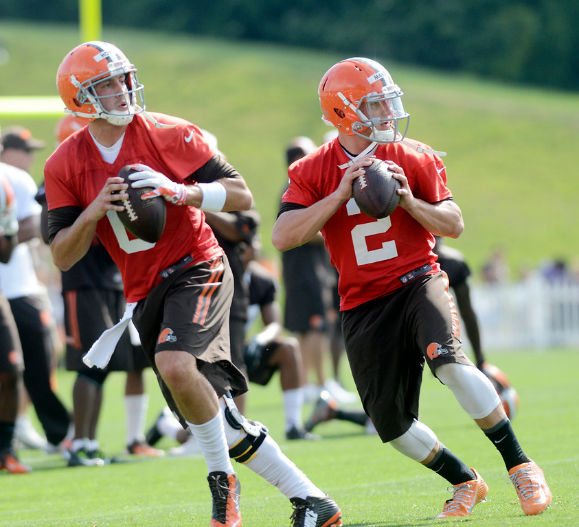 Description of . Duncan Scott/DScott@News-Herald.com Quarterbacks Brian Hoyer, left, and Johnny Manziel run passing drills as the Cleveland Browns opened training camp on July 26 with their first practice at Browns headquarters in Berea.