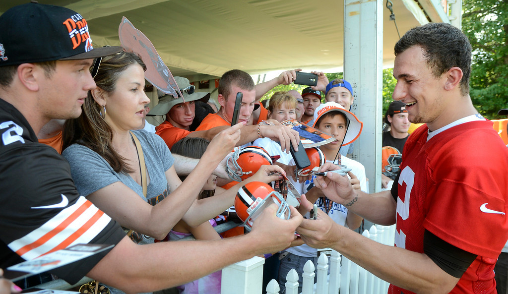Description of . Duncan Scott/DScott@News-Herald.com Johnny Manziel signs autographs after practice as the Cleveland Browns opened training camp on July 26 at their headquarters in Berea.
