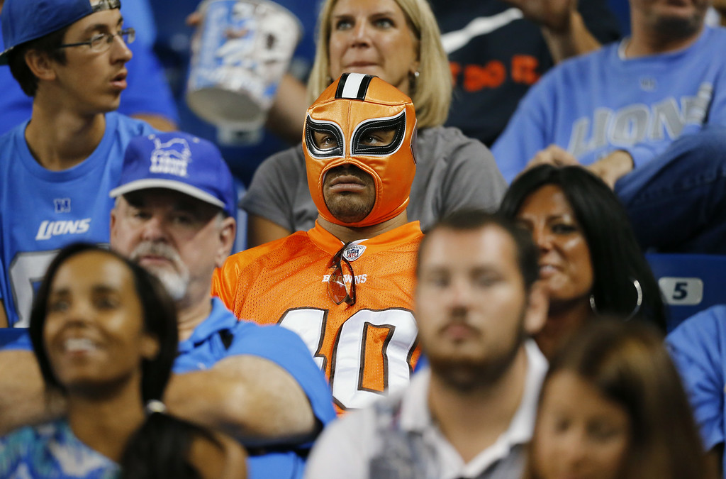 Description of . A Cleveland Browns fan sits amongst Detroit Lions fans in the first half of a preseason NFL football game at Ford Field in Detroit, Saturday, Aug. 9, 2014.  (AP Photo/Rick Osentoski)