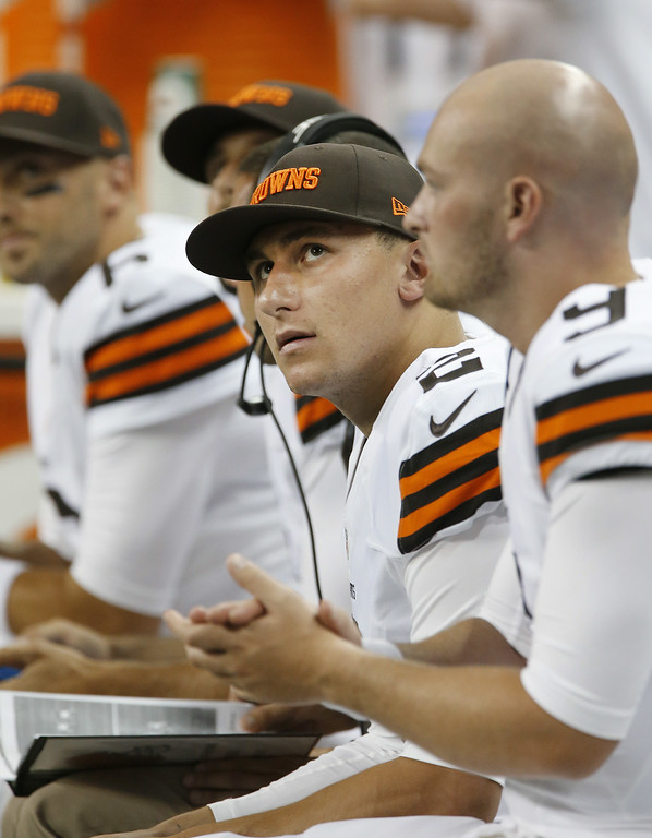 Description of . Cleveland Browns quarterback Johnny Manziel (2) watches from the bench against the Detroit Lions in the first half of a preseason NFL football game at Ford Field in Detroit, Saturday, Aug. 9, 2014. (AP Photo/Duane Burleson)