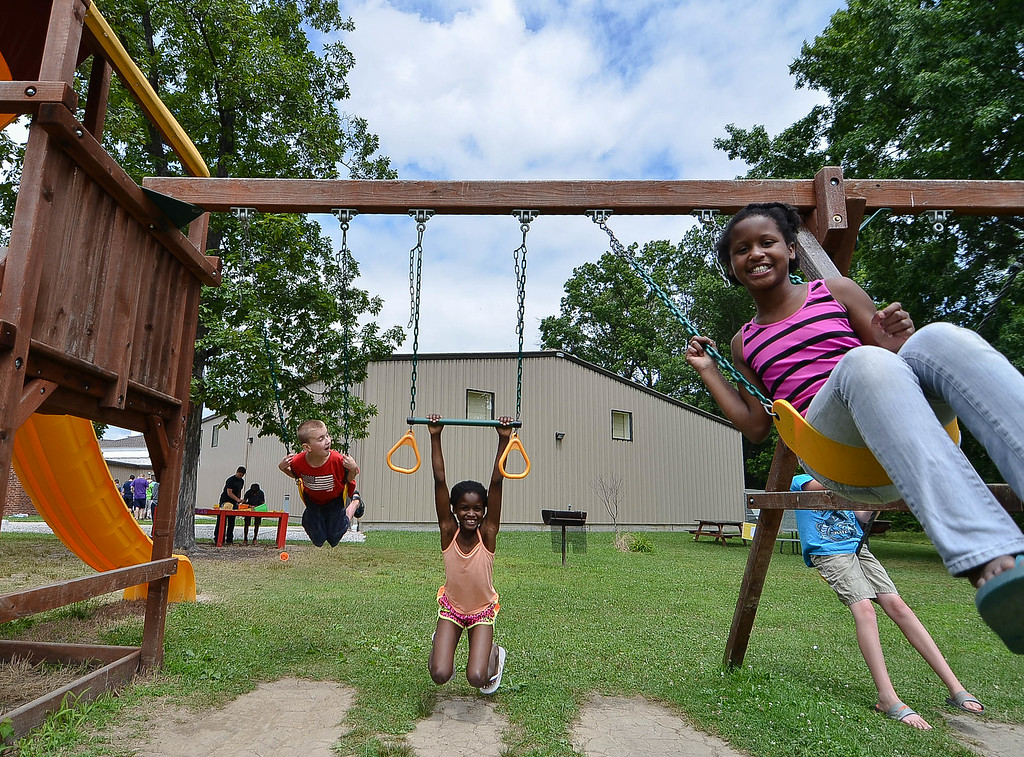 Description of . Eric Bonzar/EBonzar@morningjournal.com Ten-year-old Jamya Phillips, foreground, swings along side her sister, Jazara Phillips, 9, and 10-year-old Keith Onacila while attending the Camp I.D.E.A.S. carnival July 16.