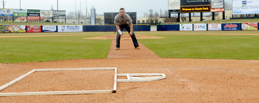 Description of . Maribeth Joeright/MJoeright@News-Herald.com<p> Grounds keeper Mike Cervella makes sure the batters box is properly aligned with home plate at Classic Park in preparation for the home opener between the Captains and the Lansing Lugnuts, April 4, 2014.