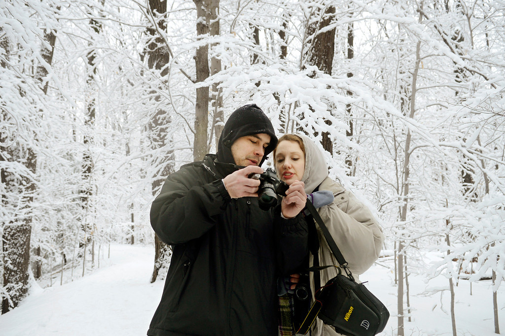 Description of . Maribeth Joeright/MJoeright@News-Herald.com Adam Dietrich, 30, of Willowick and Kate Mitchell, 29, of Kirtland look at photographs taken during a hike, Sunday at Penitentiary Glen in Kirtland. Saturday's rains eventually turned to snow which flocked all the trees, creating breathtaking scenery in every direction.
