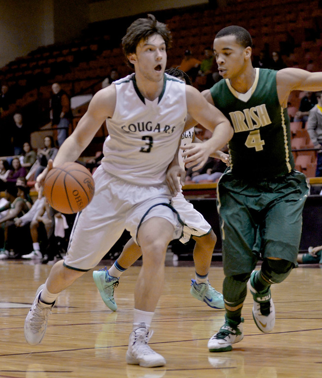 Description of . Jeff Forman/JForman@News-Herald.com Brett Nalepa, Lake Catholic,  drives down court as Josh Williams defends in the fourth quarter of the Cougars' 68-52 Division II regional semifinal loss March 13 to St. Vincent St. Mary at the Canton Civic Center.