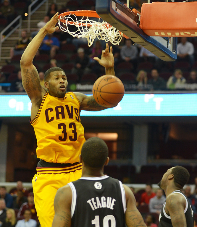 Description of . Michael Allen Blair/Digital First Media Cavs' guard Alonzo Gee dunks over Nets' guard Marquis Teague during the fourth quarter of a game April 16 at Quicken Loans Arena.