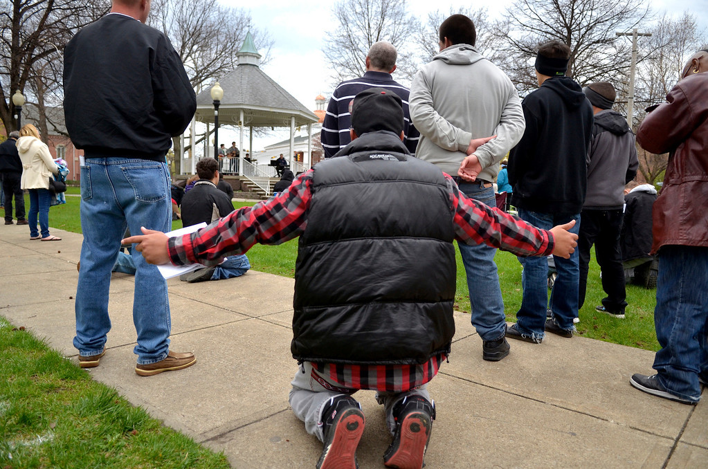 Description of . Jeff Forman/JForman@News-Herald.com Dusten Washington, of PIttsburgh, kneels in prayer  during a National Day of Prayer observance May 1 in Painesville.