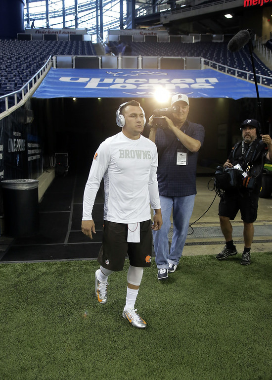 Description of . Cleveland Browns quarterback Johnny Manziel walks on to Ford Field to warm up for a preseason NFL football game against the Detroit Lions Saturday, Aug. 9, 2014, in Detroit. (AP Photo/Duane Burleson)