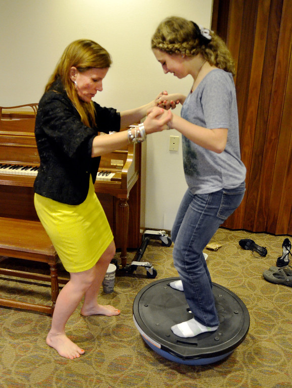 Description of . Jeff Forman/JForman@News-Herald.com Heidi Skok helps Michaela Quick stand on a Bosu ball to do a breathing exercise during a voice lesson April 14 at the Willoughby Fine Arts Association.