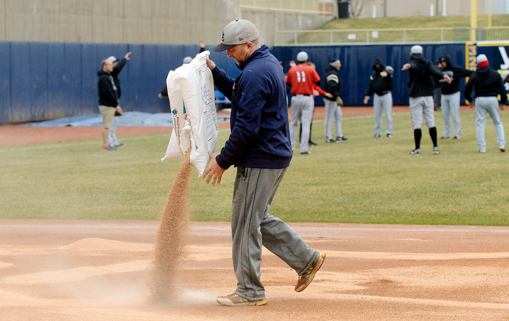 Description of . Maribeth Joeright/MJoeright@News-Herald.com<p> As members of the Lansing Lugnuts warm up, Captains head grounds keeper Dan Stricko pours a drying agent on the infield in preparation for the home opener at Classic Park, April 4, 2014.