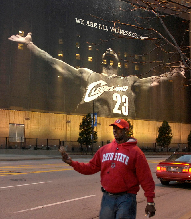Description of . Anthony Washington of Cleveland sells tickets to the Cavaliers season opener Wednesday. In the background is the new Lebron banner on one of the buildings on Ontario across from Quicken Loans Arena.