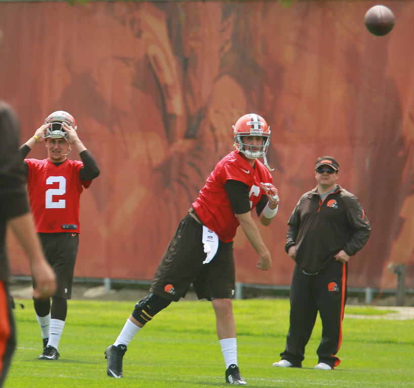 Description of . Michael Allen Blair/Digital First Media Browns' quarterback Brian Hoyer take some reps as rookie quarterback Johnny Manziel looks on at left, during organized team activities on May 21 in Berea.
