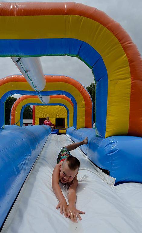 Description of . Eric Bonzar/EBonzar@morningjournal.com<p> Bruce Wilk, 7, zips down a water slide at Camp I.D.E.A.S. carnival July 16.