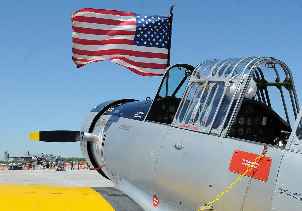 Description of . Jim Bobel/JBobel@MorningJournal.com The flag flys from the cockpit of a Navy SVN-1 Trainer and in the background sits a World War II B-25 bomber the Yankee Warrior.