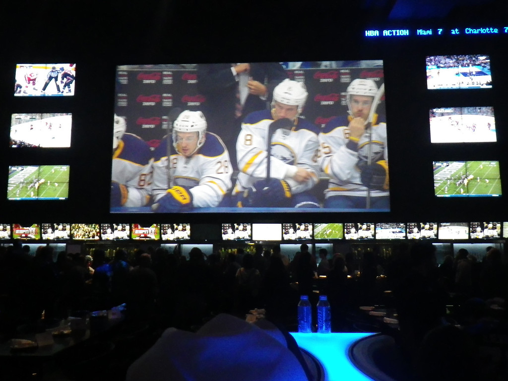 Description of . As players are introduced on the ice in the Air Canada Centre, Real  Sports Bar & Grill patrons see them on screens.