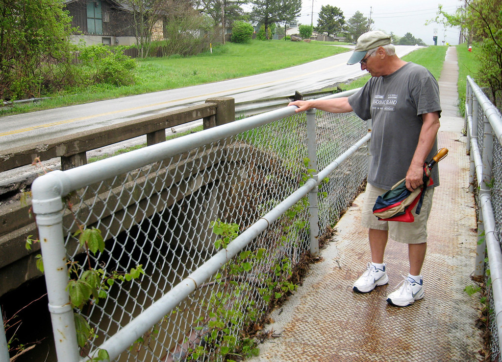 Description of . Rick Payerchin/RPayerchin@MorningJournal.com Lorain resident Cliff Piar stands at the Meister Road bridge over Martin's Run in Lorain. Piar said he wants more action from city leaders to clear out the brush and trees that block the flow of water through Martin's Run, which relatively small compared to the Black River, but is a key drainage for central and western Lorain.