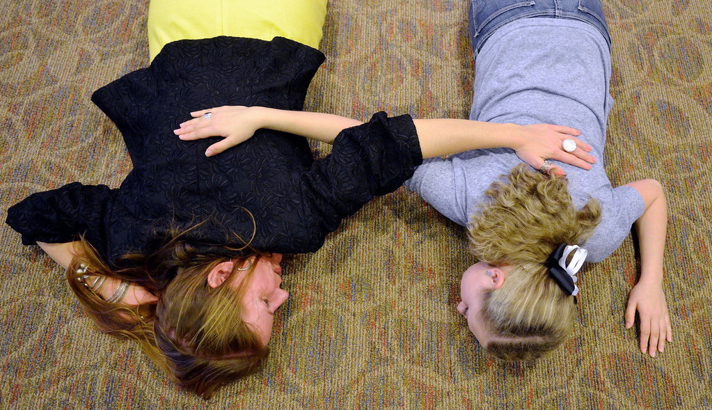 Description of . Jeff Forman/JForman@News-Herald.com Skok and Michael lie on the floor with their hands on each other's back to feel the vibrations as they vocalize.