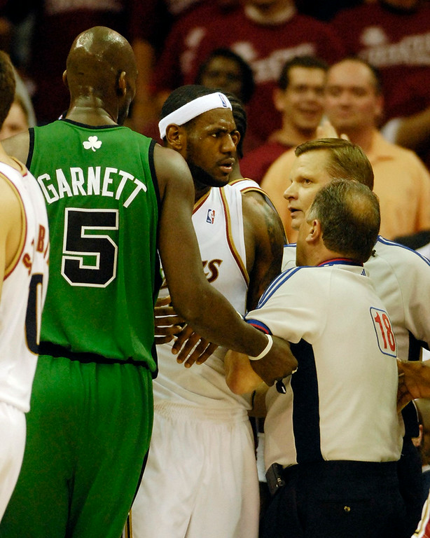 Description of . Game referees keep a hold on Cavaliers LeBron James after he was fouled by Celtics Paul Pierce during the second quarter of Game 4 of the Eastern Conference Championships Monday.