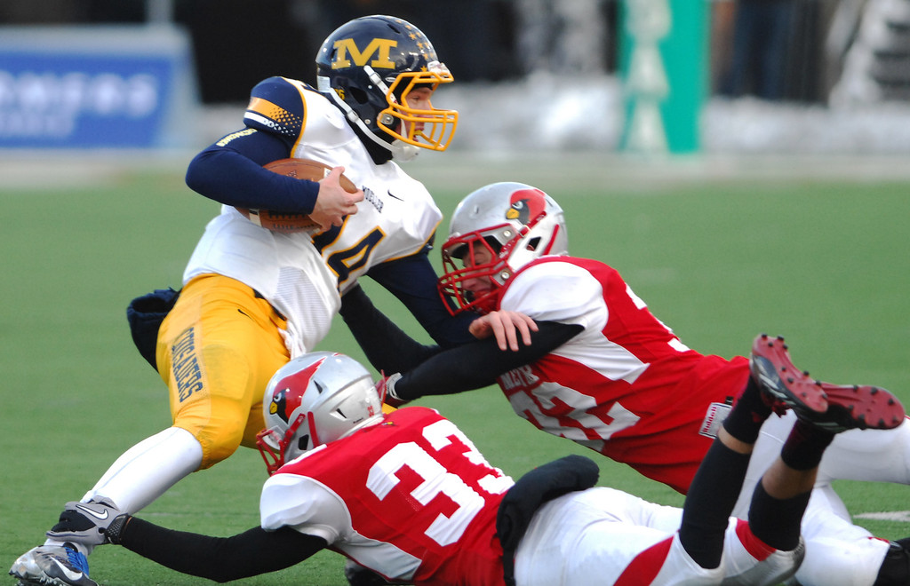 Description of . Cincinnati Moeller quarterback Gus Ragland is tackled near the line of scrimmage by Mentor linebackers Keith McCormick (33) and JD Matsko (32) during the second quarter of Saturday's Div. I state championship game at Fawcett Stadium in Canton.