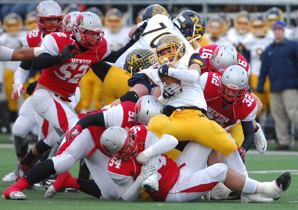 Description of . runningback Jack Gruber is wrapped up for no gain on a fourth down play by Mentor's Nico Lautanen (54) and Billy Hudson (51) during the first quarter of Saturday's Div. I state championship football game at Fawcett Stadium in Canton.
