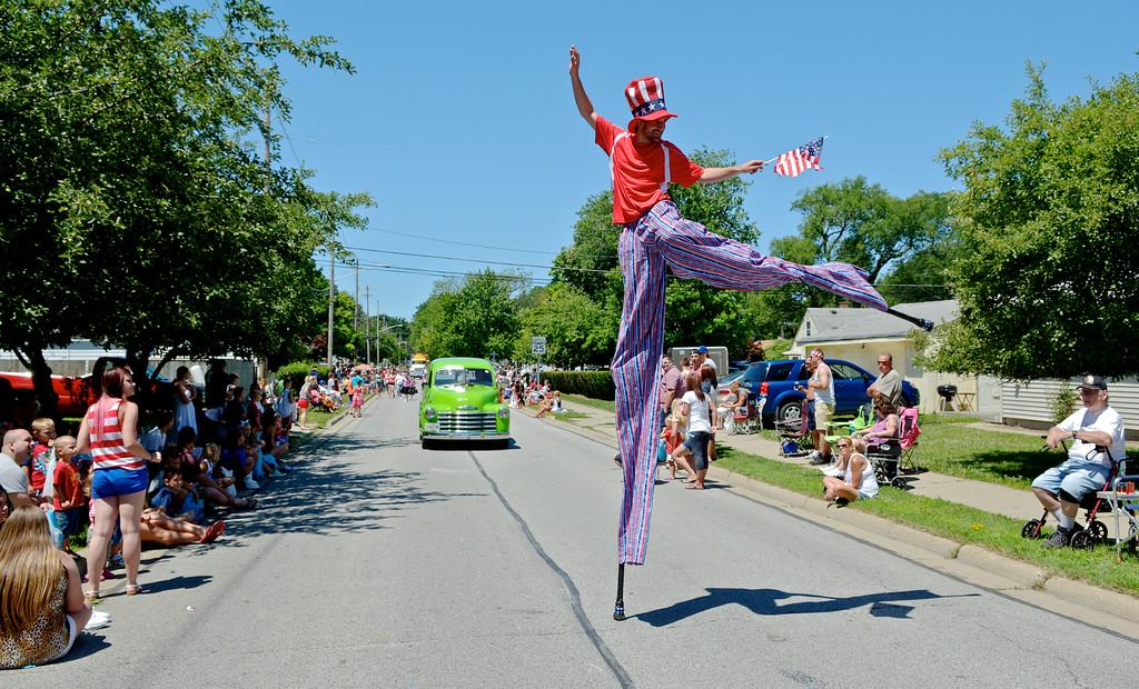 Description of . Jeff Forman/JForman@News-Herald.com Stilt walker Taliesin Haugh—Pick up Stix—marches in the Mentor Headlands July 4th Parade.