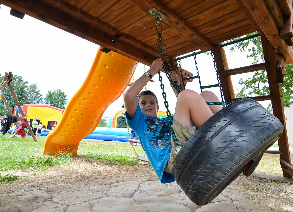Description of . Eric Bonzar/EBonzar@morningjournal.com<p> Zack Strother, 11, swings on a tire swing while attending the Camp I.D.E.A.S. carnival July 16.