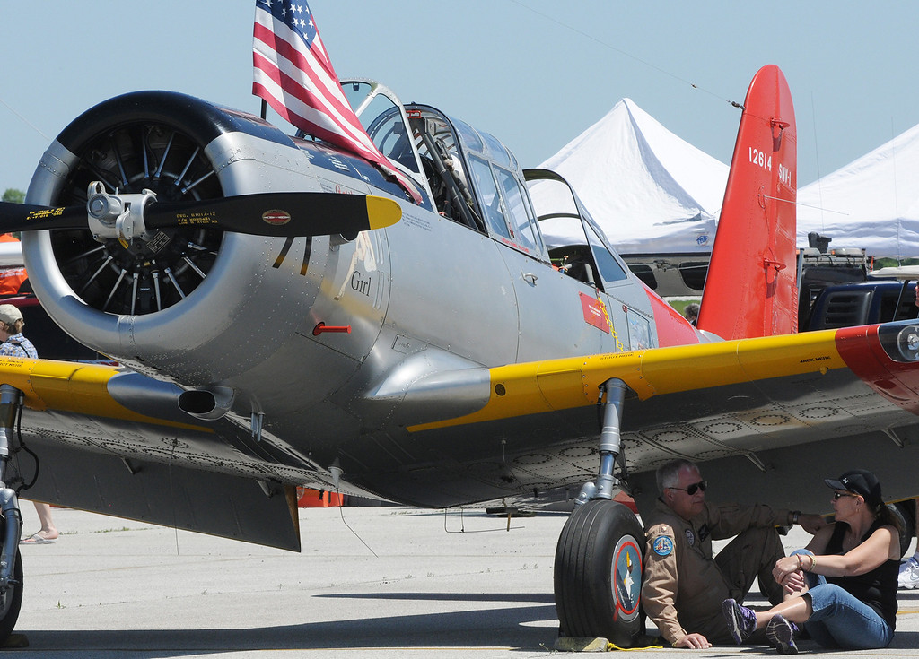Description of . Jim Bobel/JBobel@MorningJournal.com Bruce and Cheryl Koch sit in the shade underneath his Voltee Valiant SVN-1 Navy Trainer at the Discover Aviation  Air Show at the Lorain County Regional Airport.