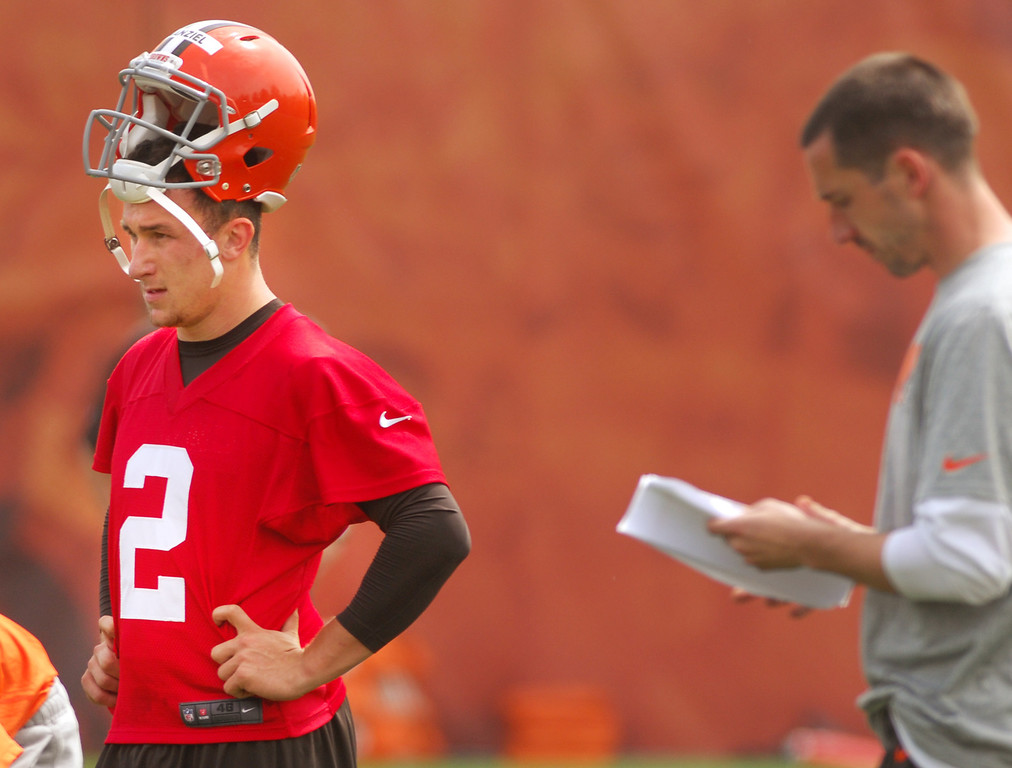 Description of . Michael Allen Blair/Digital First Media Browns' rookie quarterback Johnny Manziel takes a break alongside offensive coordinator Kyle Shanahan during organized team activities on May 21 in Berea.