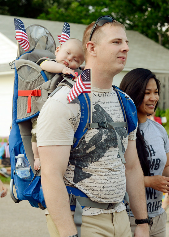 Description of . Maribeth Joeright/MJoeright@News-Herald.com<p> U.S. Army veterans Alex and Val Palmer take part in the Fairport Mardi Gras parade with their 5 month old son Abraham, July 2, 2014.