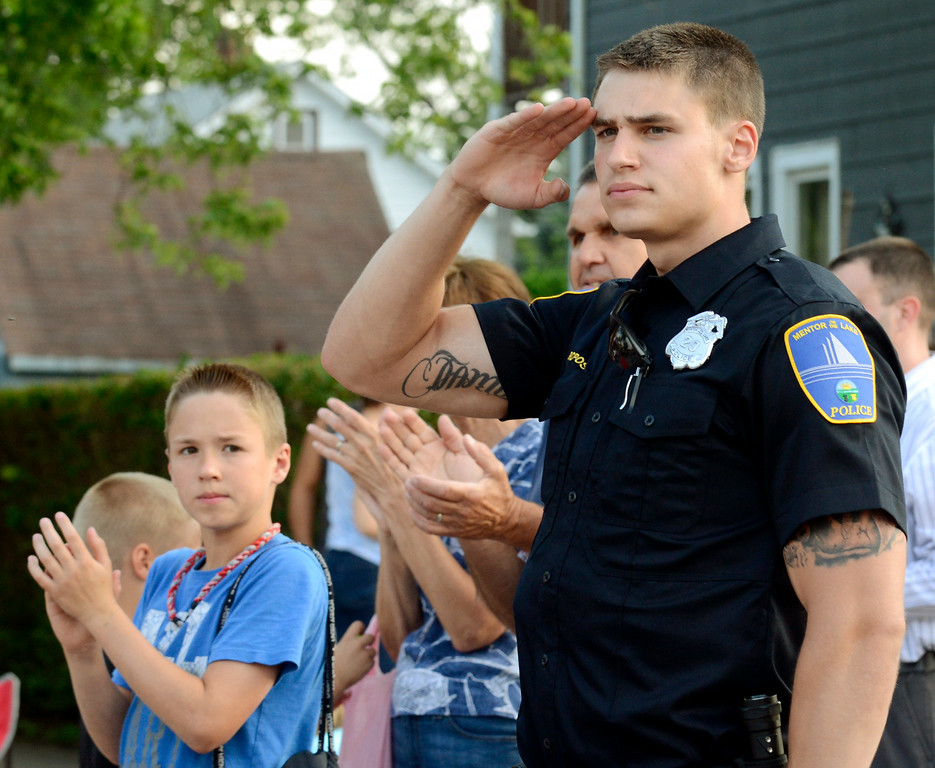 Description of . Maribeth Joeright/MJoeright@News-Herald.com<p> Zak Ropos, a patrolman with the Mentor-on-the-Lake Police Department, salutes as U.S. veterans pass by during the Fairport Harbor Mardi Gras parade.