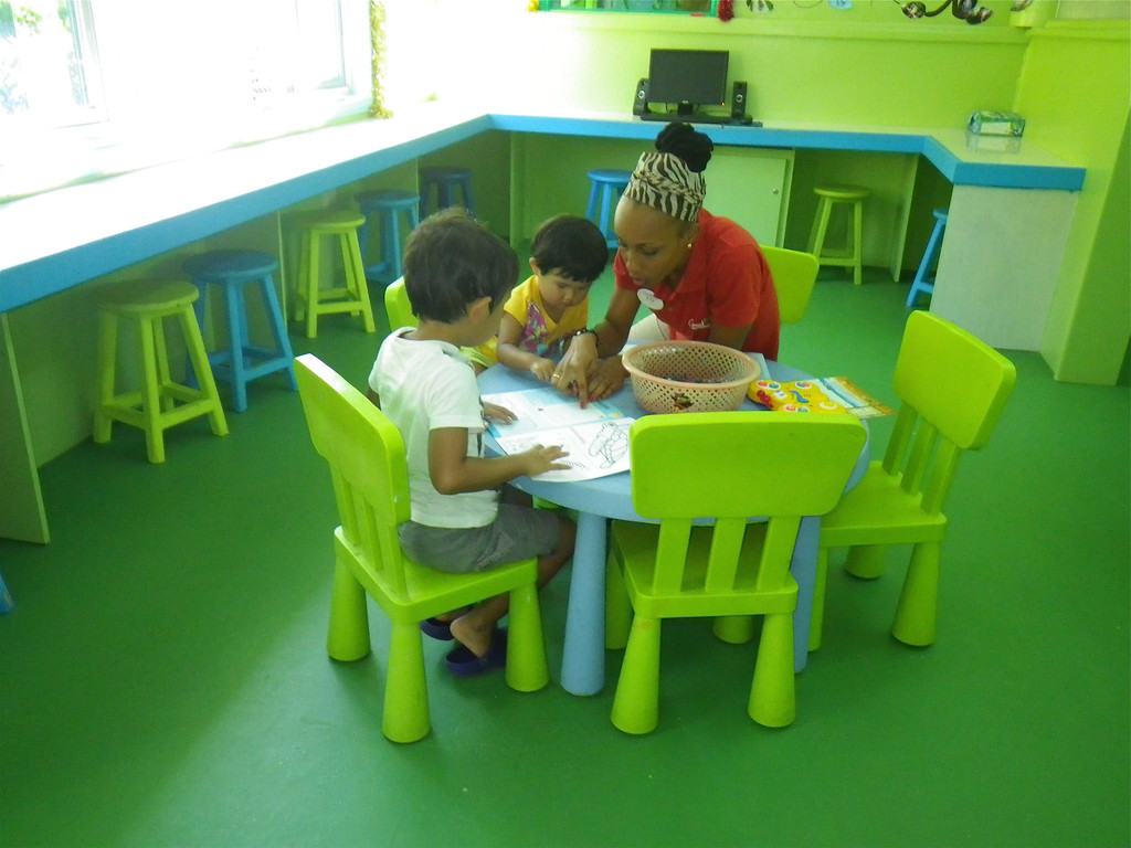Description of . Janet Podolak/JPodolak@News-Herald.com<p>                                                                               A Kidz Klub leader patiently shows two children how to color sea turtles in their workbooks.