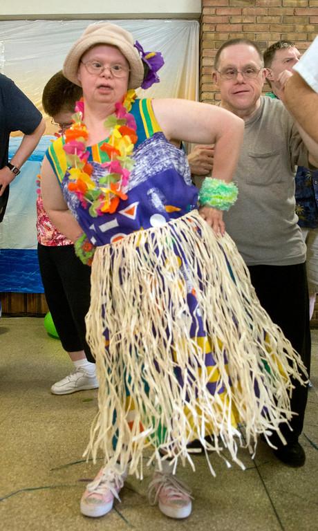 Description of . Duncan Scott/DScott@News-Herald.com Claudia Beifus learns a hula dance during a luau on June 18 at the Lake County Board of Developmental Disabilities/Deepwood Vocational Guidance Center.