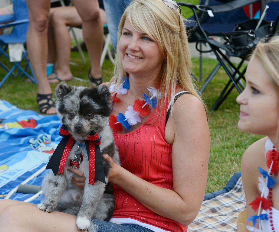 Description of . Maribeth Joeright/MJoeright@News-Herald.com<p> Christina Poole of Mentor, her daughter Tifani, 17, and their dog Baxter watch the Fairport Harbor Mardi Gras parade.