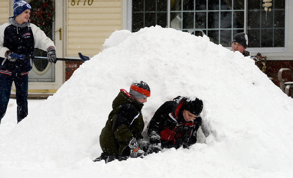 . Maribeth Joeright/MJoeright@News-Herald.com With an abundance of snow, Dale Patterson, 13, from left, Timmy McGuinness, 10, Marco Toth, 12, and Tyler Koller, 15, decided to build an igloo in front of the McGuinness home on Doorwood Drive in Mentor, Wednesday.
