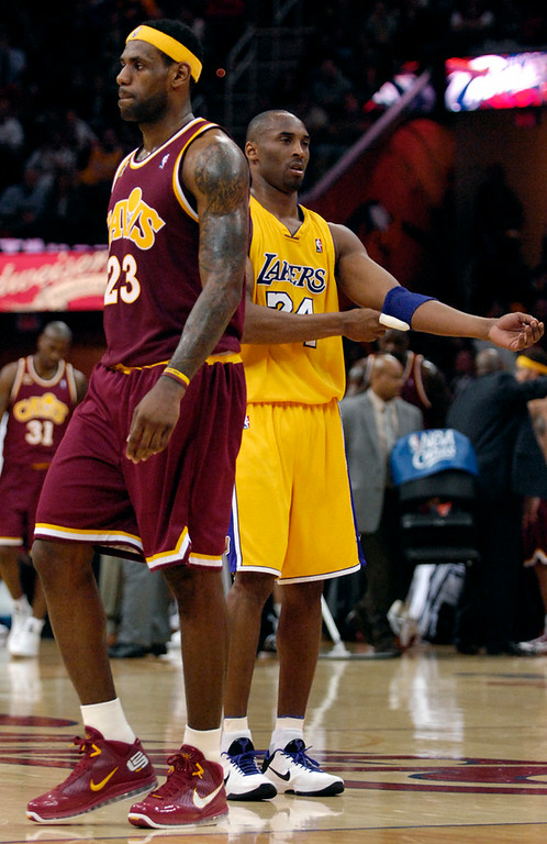 . Jeff Forman/JForman@News-Herald.com LeBron James walks by Kobe Bryant during a pause in the game Thursday at Quicken Loans Arena.