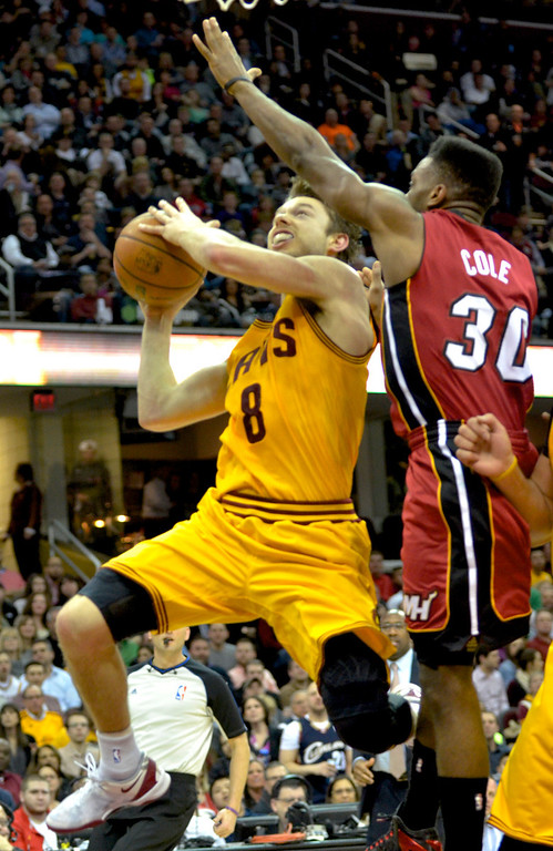 . Jeff Forman/JForman@News-Herald.com Matthew Dellavedova takes a shot as the Heat\'s Norris Cole defends in the first half of the Cavaliers\' 100-96 loss March 18 at Quicken Loans Arena.