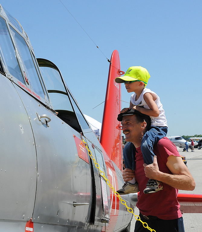 . Jim Bobel/JBobel@MorningJournal.com Four year old Tommy McEwen checks out the cockpit of a Navy trainer from the shoulders of his grandfather Dale Housley.