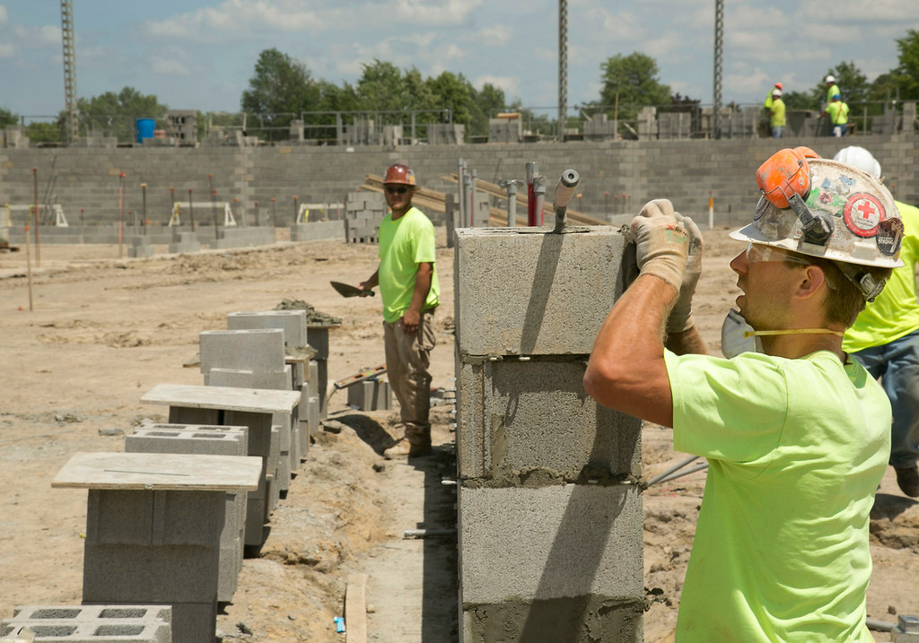 . Michael Allen Blair/MBlair@MorningJournal.com Brick layers assemble a wall of what will be the part of the Lorain Sports Hall of Fame and Lorain County Historical Society inside of the new Lorain Admiral King High School in Lorain on June 30.