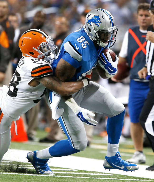 . Detroit Lions tight end Eric Ebron (85) is brought down by Cleveland Browns outside linebacker Christian Kirksey (58) in the first half of a preseason NFL football game at Ford Field in Detroit, Saturday, Aug. 9, 2014.  (AP Photo/Duane Burleson)