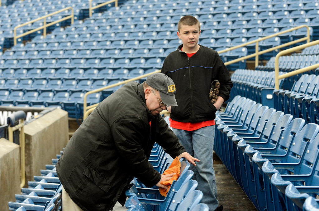 . Maribeth Joeright/MJoeright@News-Herald.com<p> Bob Dew of Willowick dries off the seat at Classic Park in preparation for the Lake County Captains opener as Andrew Guarino keeps him company. A heavy rain fell earlier creating much work for Dew and the other ushers before the start of the game.