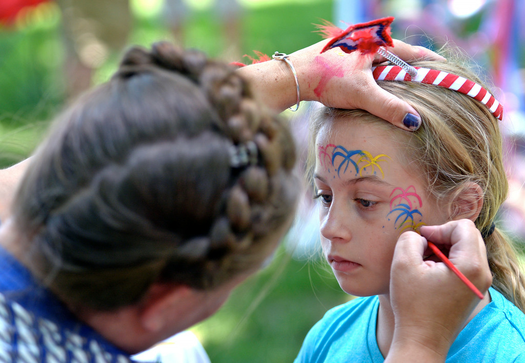 . Jeff Forman/JForman@News-Herald.com Rachel Park paints fireworks on Meadow Pike\'s face during the July 4th Old Glory Day celebration on Chardon Square. Meadow, 9, was at the event with her father, David Pike.