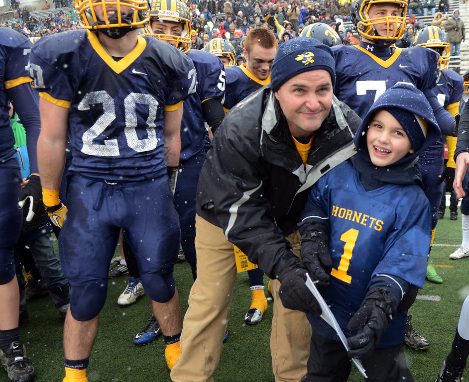 . Duncan Scott/DScott@News-Herald.com Kirtland\'s coach Tiger Laverde and his son enjoy the final moments Kirtland\'s 44-16 victory over Wayne Trace Friday in the  Division VI state championship game at Fawcett Stadium in Canton.