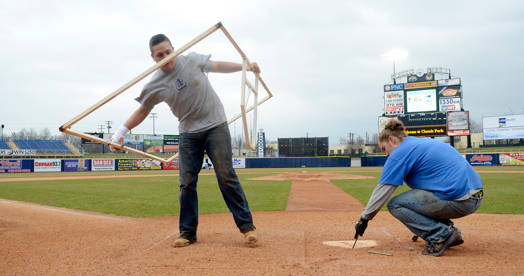 . Maribeth Joeright/MJoeright@News-Herald.com Grounds keepers Mike Cervella and Brittany Deas prepare the home plate area at Classic for the Captains home opener against the Lansing Lugnuts, April 4, 2014.