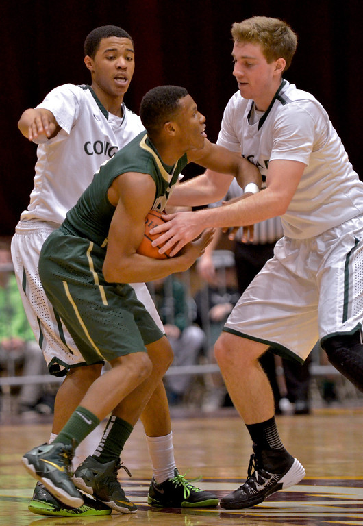 . Jeff Forman/JForman@News-Herald.com Ben Meola, Lake Catholic,  fights Jarel Woolridge for the ball during the Cougar\'s 68-52 Division II regional semifinal loss March 13 to St. Vincent St. Mary at the Canton Civic Center.