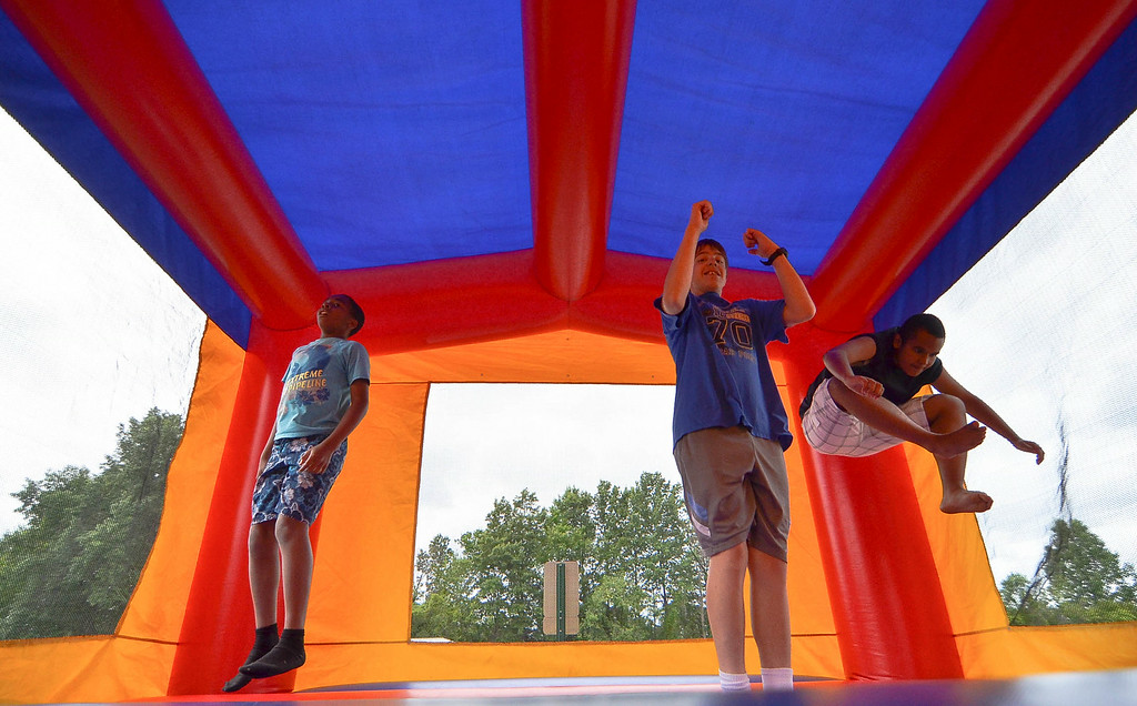 . Eric Bonzar/EBonzar@morningjournal.com<p> A group bounces around in a bouncy house during Camp I.D.E.A.S. July 16.