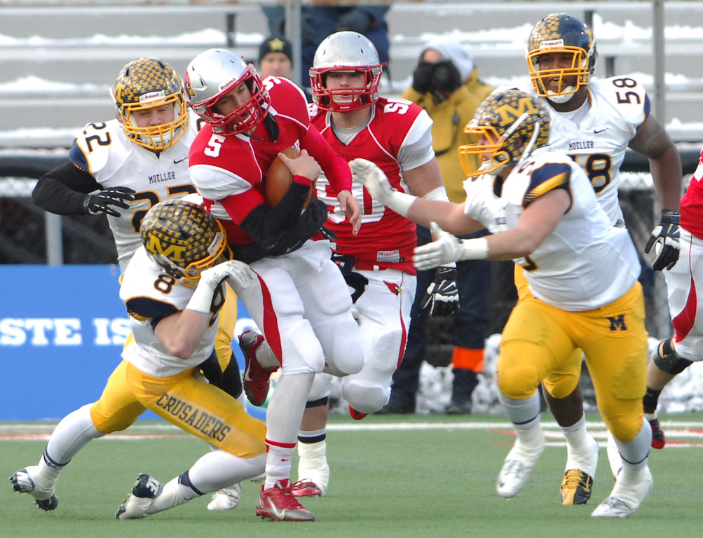 . Michael Allen Blair/ MBlair@News-Herald.com Mentor quarterback Conner Krizancic scrambles from the pocket under pressure from Cincinnati Moeller  linebacker Will Mercurio during the first quarter of Saturday\'s Div. I state championship game at Fawcett Stadium in Canton.