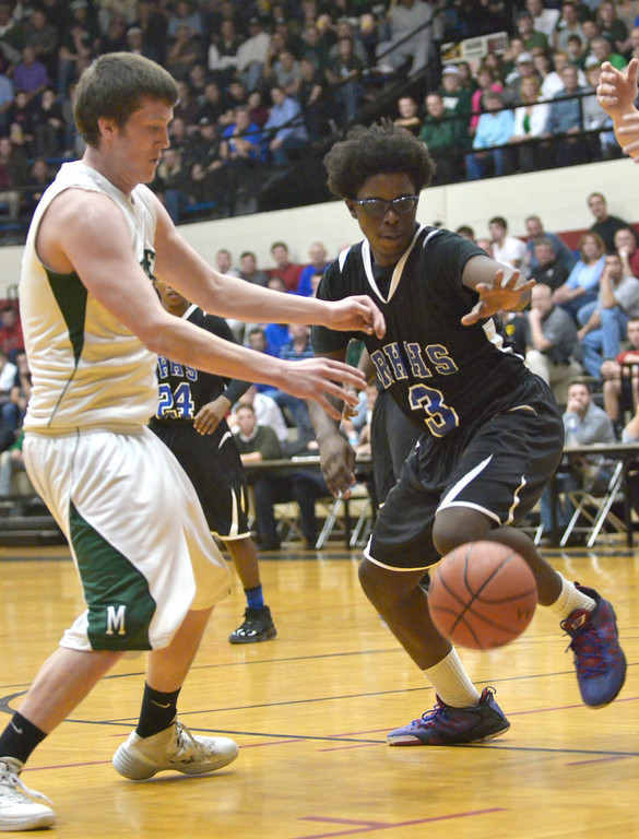 . Jeff Forman/JForman@News-Herald.com Mory Bamba, Richmond Heights, reaches for a loose ball in the first quarter of the Spartans\' 59-45 Division IV regional semifinal win over Malvern March 11 at the Canton Field House.