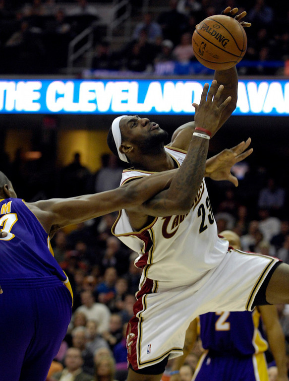 . Michael Blair/MBlair@News-Herald.com The Cavs\' LeBron James is fouled from behind by Laker\'s forward lamr Odom as he drives to the basket during the fourth quarter of Thursday\'s game at The Q.