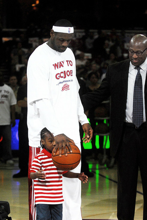 . Bridget Commisso/BCommisso@News-Herald.com  Lebron James hands his son,Lebron Jr., the ball before the start of the game Wednesday night. James was honored as the Cavs all timehighest scorer.