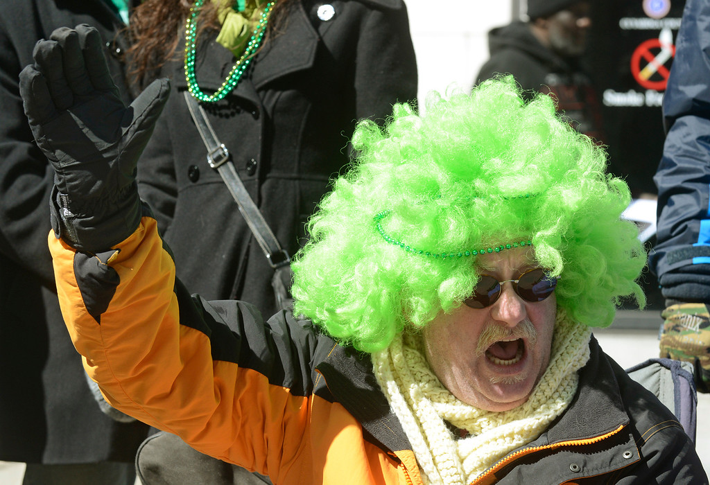 . Maribeth Joeright/MJoeright@News-Herald.com Chris Gilchrist of Chardon wears his green wig with pride as he waves to participants in the 147th annual St. Patrick\'s Day parade in Cleveland, March 17, 2014.