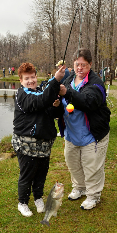 . Jeff Forman/JForman@News-Herald.com Cori Sayre, right, helps Carol Jamieson bring in a fish during the Lake Metroparks Fantastic Fishing program for people with disabilities April 30 at Hidden Lake in Leroy Township.